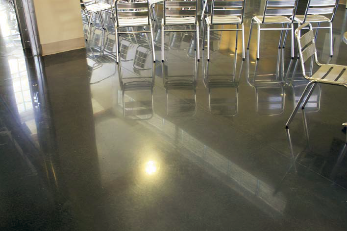 Break room that has chairs lined throughout has gray polished concrete floors.
