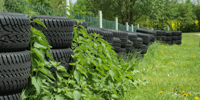 Lines of rubber tires along the fence line and green grass.