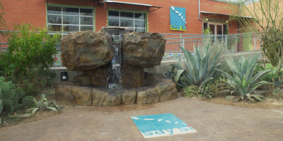 Front entrance of Say Si with a fountain, stamped concrete and a stained logo.