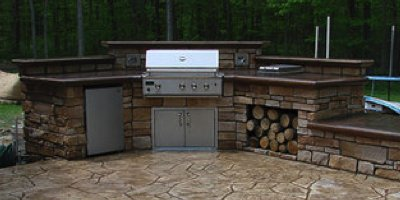 An inviting outdoor kitchen with concrete countertops and a stamped concrete patio in a cold climate.