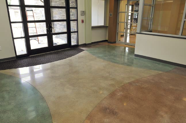 Concrete floor in a lobby has four distinct areas that are stained with different colors.