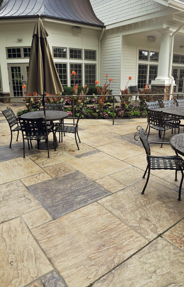 Stamped concrete patio with patio furniture and umbrellas against a white house.