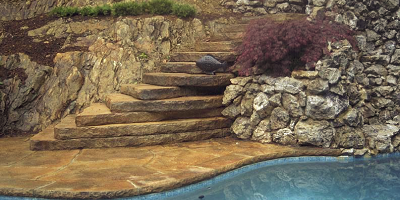 Concrete Steps that look like natural stone lead up the side of this hilly oasis.