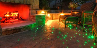 Fiber optic light glows in this outdoor living space with carved concrete fireplace and a stamped concrete patio.