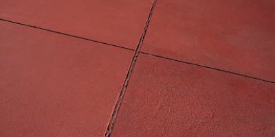 A close up look of control joints on a red concrete patio.