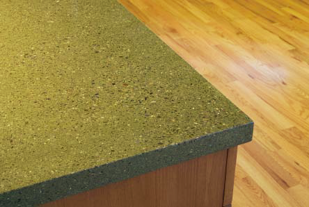 A corner of a concrete countertop that is green with black and white aggregate.
