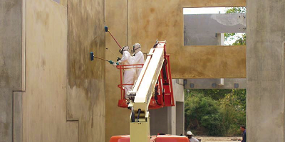 Two people in white coveralls on a boom lift acid staining walls.