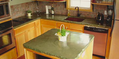 A concrete countertop in green makes this kitchen pop.