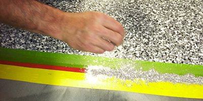 Applying metallics to the concrete with the help of green, yellow and red tape.
