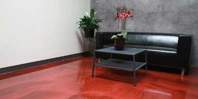 A red metallic epoxy on a room with a black leather couch.