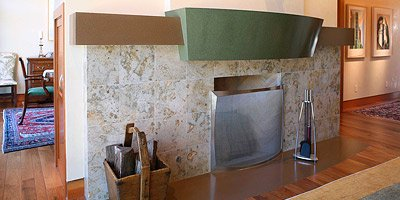 Green precast concrete fireplace mantle in a beautiful living room with light woodwork.