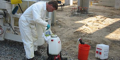 Construction worker filling up a pump sprayer with a fix for concrete staining projects.