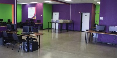 Polished concrete in a high school space that has purple walls and lime green accents.