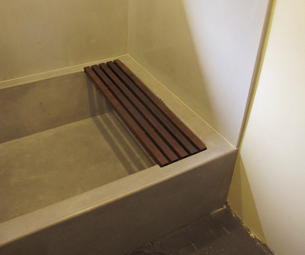 Concrete tub in a bathroom with a wood rack for setting items on.