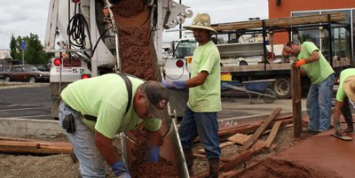 Construction crew pouring integral colored / pigmented red concrete into a sidewalk form.