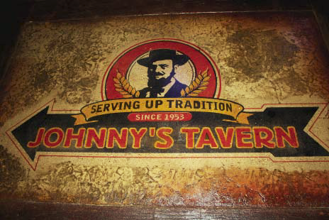 A Johnny's Tavern logo stenciled and colored on brown stained concrete.