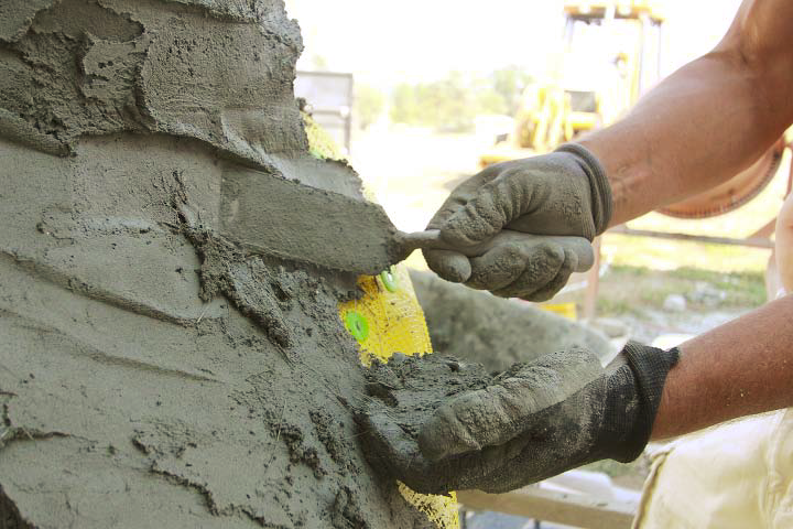 A person uses a carving trowel to carve and place concrete