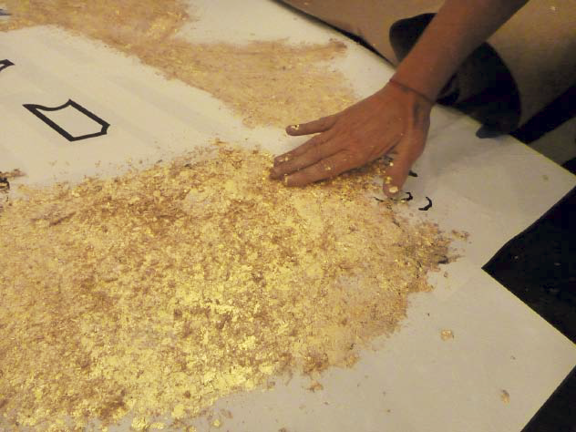 Applying the gold metallic flakes to the logo stencil.