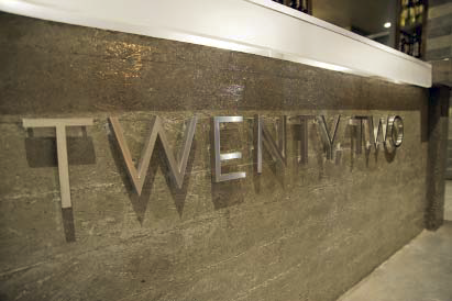 Metal letters raised off of a concrete wall that doubles as a bar lobby counter.