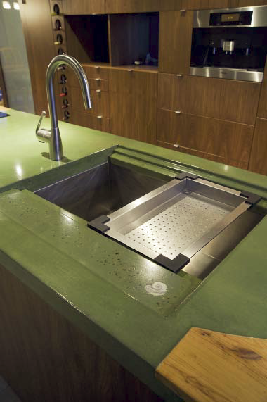 Green concrete countertop with a built in drainboard.