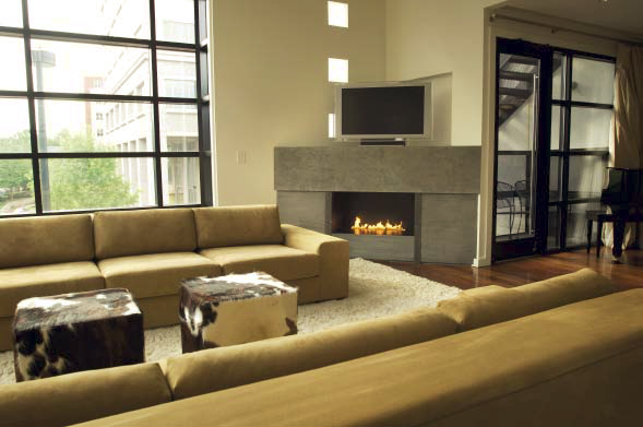 A concrete fireplace with a flat screen television on top of it in a room with two couches and cow skin covered ottomans.