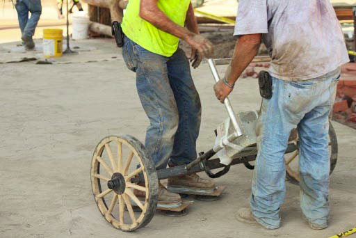 Two crew members work on equipment that helps give the look of the old west.