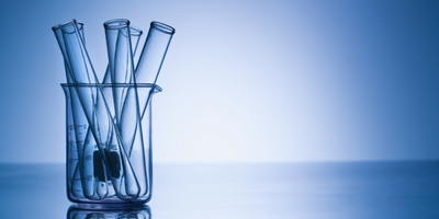 Test tubes for chemistry in a jar with a blue background behind it.