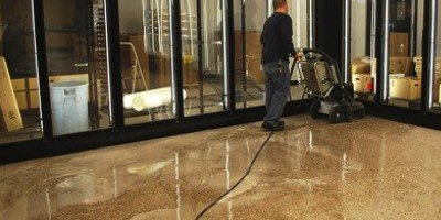 Using an HTC concrete polishing machine, a man is maintaining the concrete in a Wawa store in the Northeast United States.