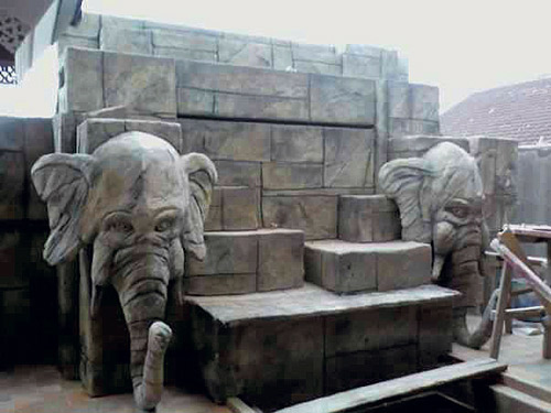Two elephant heads flank this block wall made of concrete by Thom Hunt.