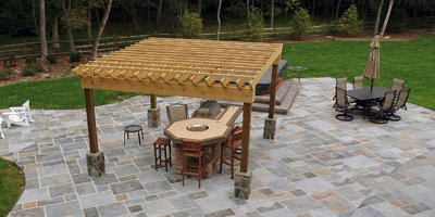 Stamped concrete patio with pergola and fire pit in muted slate colors.
