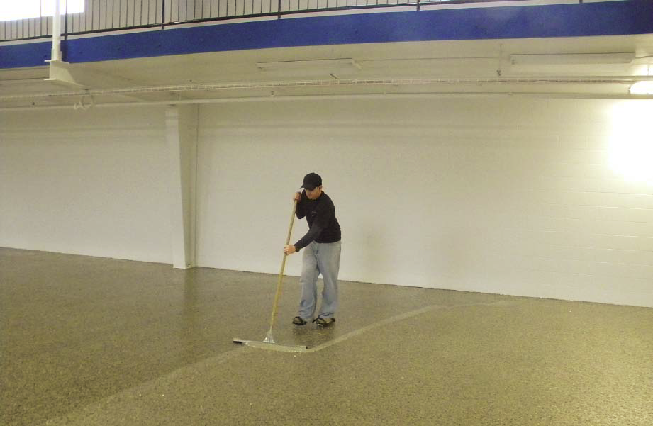 Crew members for Nashville-based Fuller Industries Inc. install a mica chip floor with roller brushes at a Nashville book and CD store using mica chips from Torginol and Florock polymers.