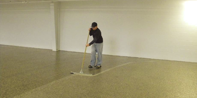 Rolling mica flakes onto a concrete floor.