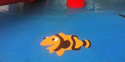 A rubber surfaced floor that has been artistically upgraded with an image of a clown fish.