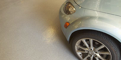 Westcoat's Quartz system on a garage floor with a gray car parked on it.
