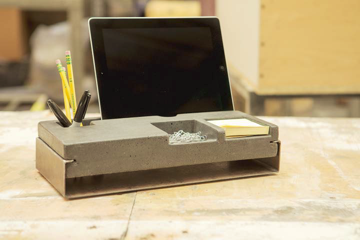 A concrete desk organizer that has a tablet holder.