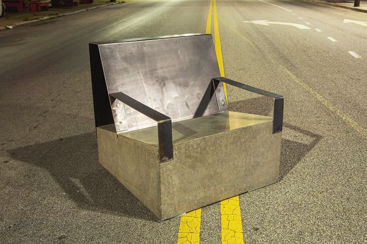 A concrete chair with metal arm rests sitting in the middle of the highway.