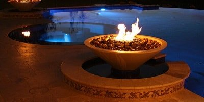 Concrete fire pit displays in front of a smooth as glass swimming pool during a sunset.