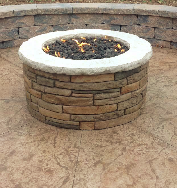Concrete fire pit with carved concrete sitting on top of stamped concrete.