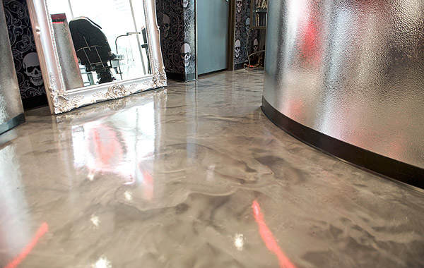 Metallic epoxy concrete floor in a swirling white and platinum grace this busy floor