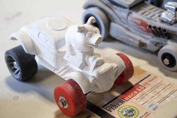 concrete derby car with a pig in an old hot rod car