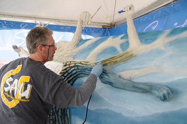 Ochs airbrushes Smith's water-based concrete stain onto the surface. Since Smith Paint is known for its colors, he went with rich hues for the branches rather than using the natural colors of a cottonwood.