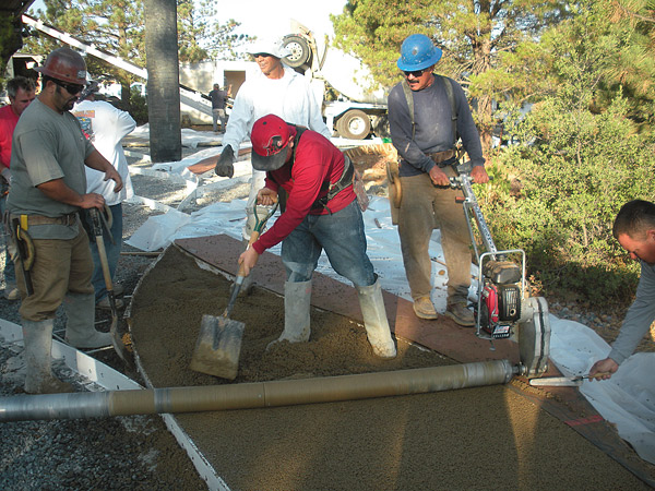 pouring a pervious driveway The crew pours a section of the pervious driveway, compacting it with an aluminum roller screed.