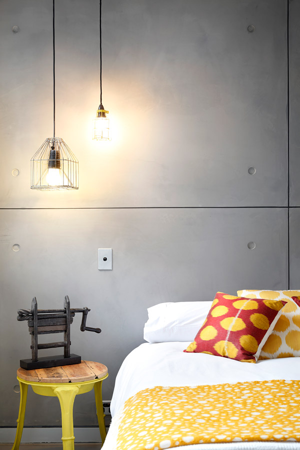 grey wall with yellow bed and colorful pillows