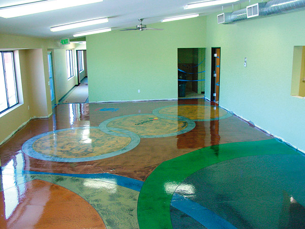 Concrete contractors use stains or dyes to color on a concrete floor adding delightful abstract artwork.