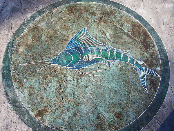 concrete artists use color wheel to create blue green marlin swordfish within circle on brown textured concrete floor.
