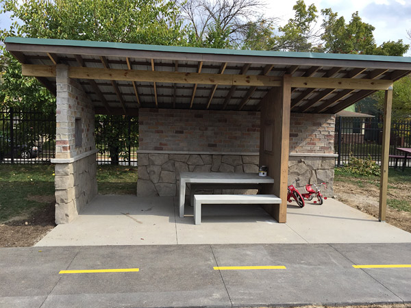 concrete bench and table featured inside rock picnic shelter