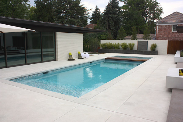 Rectangle luxurious pool with cool chairs, white concrete pool balls, concrete with a smooth, brushed finish, one awesome pool deck