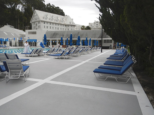 concrete pool deck with blue chairs