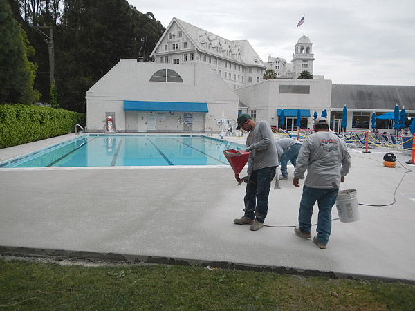 pool deck with workers applying and overlay