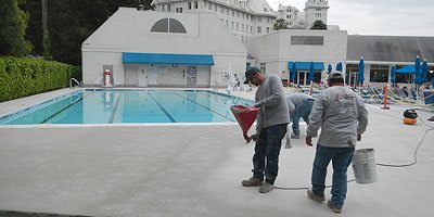 contractors pouring concrete near pool